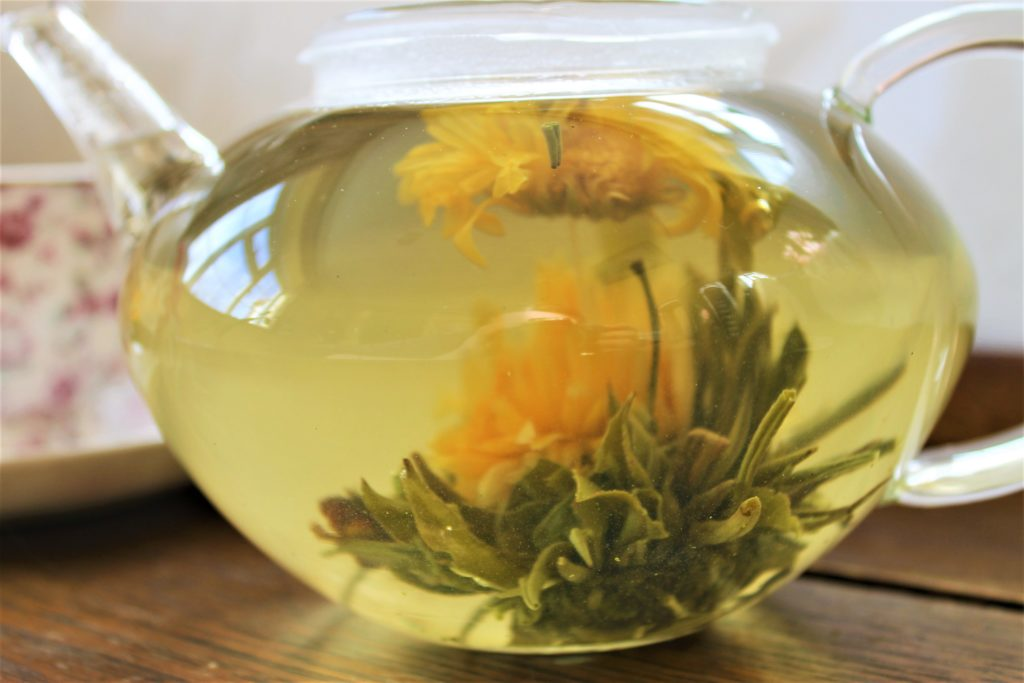 Marigold blooming tea in glass teapot