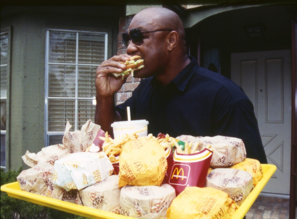 George Foreman with a huge meal with cheeseburgers fries and large drink