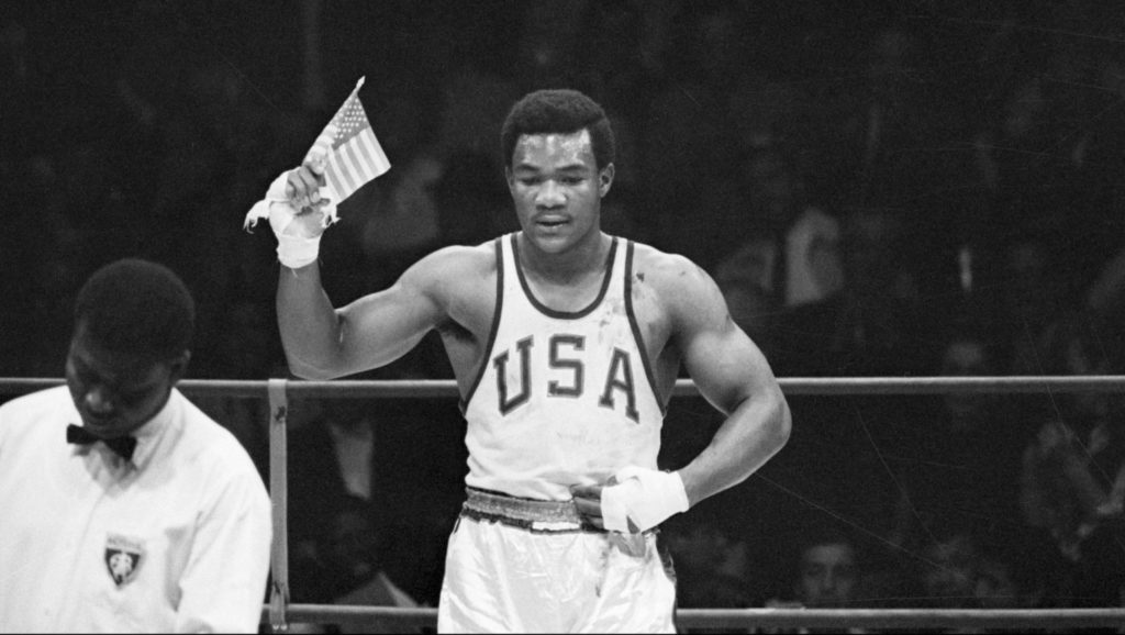 George Foreman waving flag at the Olympic games where he won the gold medal
