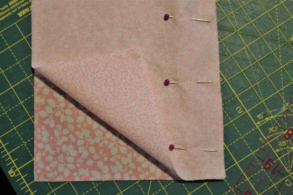 pinning together pink fabric squares