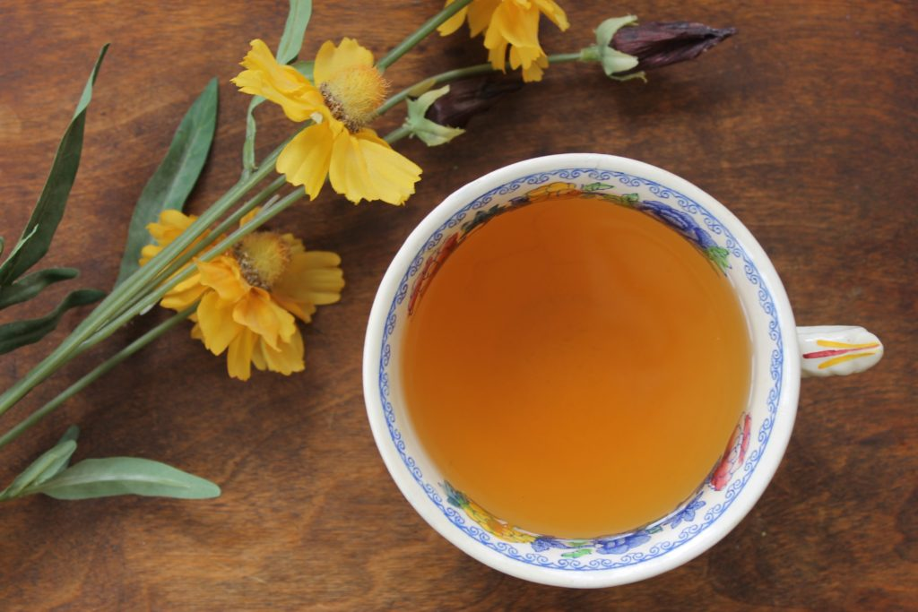 cinnamon and ginger tea in cup with flowers
